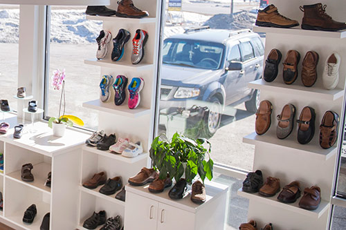 Full wall display of different types of orthopedic footwear at Azilda Family Foot Care in Azilda, ON